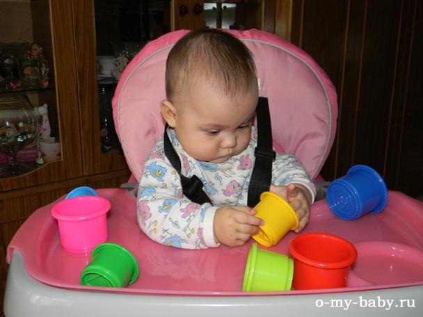 Девочка сидит и играет.