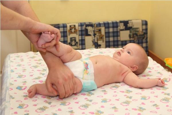 Родитель помогает малышу перевернуться