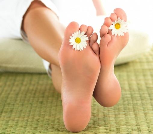 Голые ступни ног с ромашками