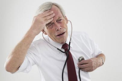 Пожилой мужчина с фонендоскопом в ушах слушает свое сердце