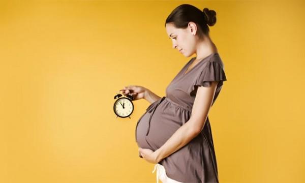 Беременная женщина держит в руке будильник