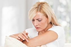 Женщина рассматривает папиллому на руке