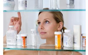 женщина выбирает осматривает лекарства на полке