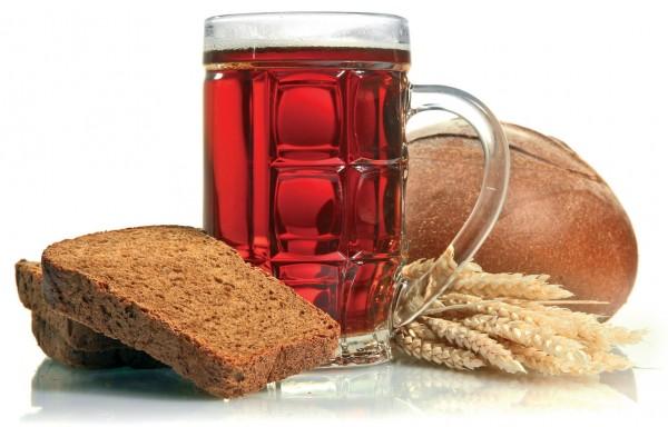 Бокал с квасом рядом с хлебом и колосьями