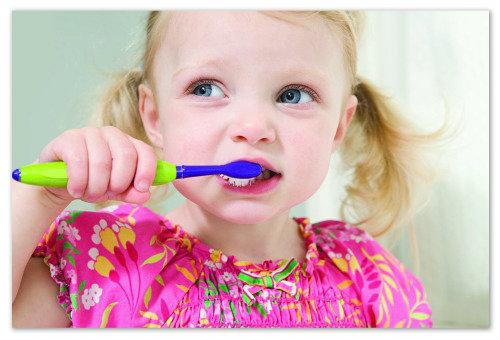 Девочка чистит зубы.