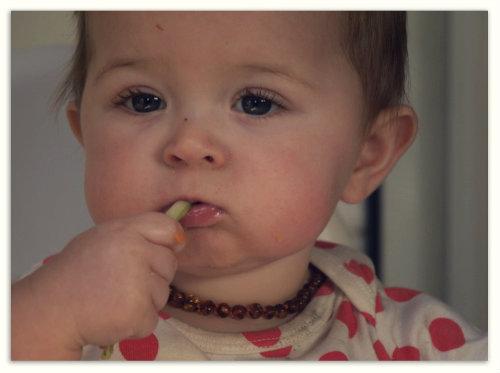 Девочка жует огурец.