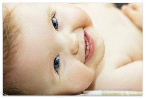 Ребенок улыбается лежит.