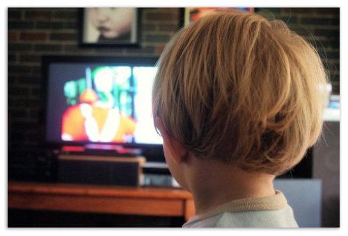 Мальчик смотрит телевизор.