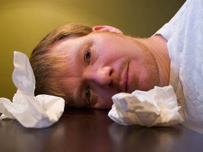 Мужчина страдает от насморка