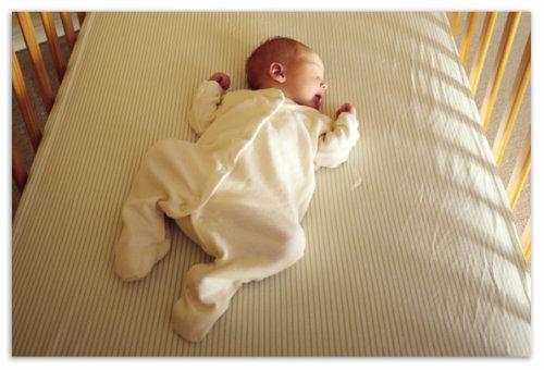 Ребенок спит в кроватке.