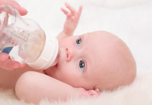 Ребёнок пьёт из бутылочки