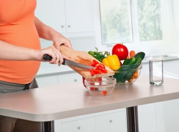 Беременная женщина нарезает овощи на кухне