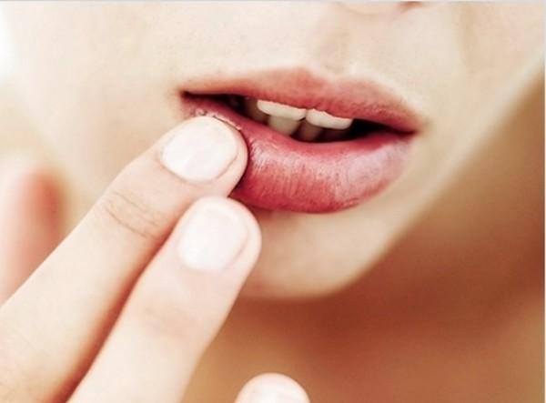 Девушка трогает пальцами свои губы