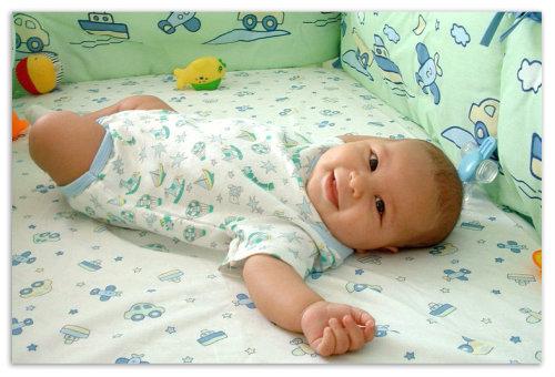 Мальчик в кроватке.