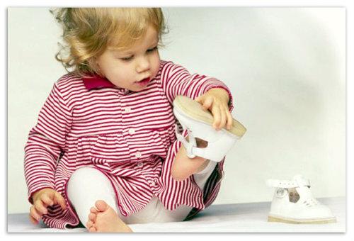 Девочка одевает сандалии.